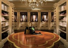 this dressing room has custom cabinetry, crystal chandelier, gorgeous table ♥♥