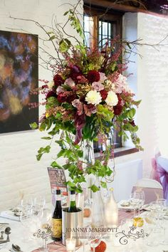 Autumnal top table arrangement, mauve, cream and maroon colour theme. Made of mauve roses, maroon- red carnations, heather, twigs, dahlias, ivy and garden hydrangeas.