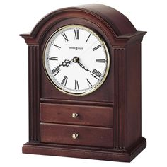 635112 Howard Miller Quartz Mantel Clock jewelry drawers Cherry KAYLA. The addition of two felt-lined jewelry drawers make this arch top clock a thoughtful and unique choice.Fluted columns, and a polished brass tone bezel create a classic appeal.Off-white dial with black Roman numerals, black serpentine hands, and convex glass crystal.Finished in Windsor Cherry on select hardwoods and veneers.