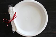 Throw a more organized picnic or outdoor party by tying utensils and napkins to paper plates for easy pickup. Also helps to free up hands! #organization