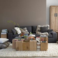 modern gray sofa, set of square wood tree trunks as coffee table