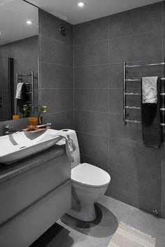 Jednolite szare kafle na ścianach i podłodze, chromowany grzejnik, prosta szafka z aluminiowymi dyskretnymi uchwytami tworzą nowoczesny wystrój tej łazienki. Blat pod umywalką dla spójności również wyłożono identycznymi płytkami. Minimalistyczny chłód wnętrza przełamuje bawełniany dywanik w etniczne wzory.