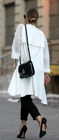 How To Wear A Black And White Outfit: Helena Glazer is wearing a white trench coat and black trousers from DKNY with a pair of Jimmy Choo heels