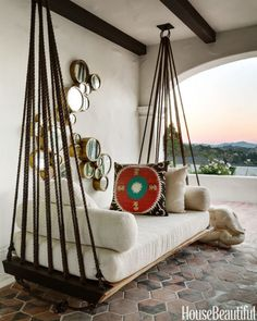 Snuggling up on an outdoor swing looks like an all-weather activity when it's positioned in a snug alcove. Designer Erin Martin improvised this divan for a Spanish Colonial's loggia using rope, metal rings and wood. Click through for more ideas for cozy outdoor fall decorations.