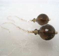 Gorgeous faceted Smoky Quartz rounds are adorned with Bali spiral beads and Black Diamond Swarovski crystals. They swing from tiny sterling silver cable chain and handmade sterling silver ear wires. Measures 2 inches in length from top of ear wire to bottom of bead. These will be promptly made to order and quickly shipped. Please feel free to contact me if you would prefer this design with a different color scheme. I would love to work with you.