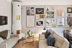 salon ze skandynawski piecem ceramicznym,biała ściana z obrazami,fotografie i plakaty na białej ścianie,domowa galeria palaktów nad białą komodą w salonie,skandynawska jadalnia z grafikami na białej ścianie,jak stworzyć domową galerię na ścianie,plakaty i grafiki na scianie,jakie plakaty pasują do salonu w stylu skandybnawskim,jak wieszać obrazy i plakaty na ścianie,skandybnawskie plakaty i grafiki w salonie