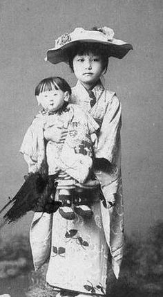 Japanese girl with doll, kimono and hat. 1912.