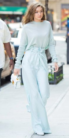 Gigi Hadid stunned in an all mint ensemble while out in the New York City breeze. The model kept it cool in a light knit tucked into billowy high rise trousers cinched in at the waist. Simple white accessories—a mini top handle bag and pointed toe boots—kept the look fresh.