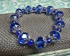 SALE Breathtaking Sapphire Gemcut Glass Oval Beaded Bracelet w/White Silver Swirled Caps & Small Acrylic Round Cobalt Beads FREE SHIPPING - Only.$6.45 on Etsy! https://www.etsy.com/listing/229288897/sale-breathtaking-sapphire-gemcut-glass