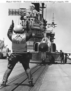 USS Midway Flight Deck Director signals an Phantom II fighter into position on the starboard catapult in preparation for launching. 5 August Photo Kevin Freedman x Us Military Aircraft, Us Navy Aircraft, Navy Aircraft Carrier, Military Jets, Diorama, Old Brown Shoe, The Fog Of War, F4 Phantom, Vietnam War Photos