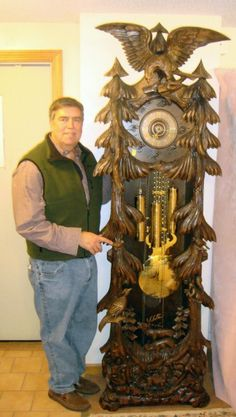 Magnificent German Carved Black Forest Grandfather Clock. 3 weight large brass pendulum. All engraved, full spread eagle at top. Birds, squirrel w/nuts, pheasant, 2 deer with full rack with pine trees in the forest. A stunning example of Black Forest carving.