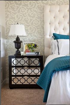 Gorgeous turquoise blue & espresso brown bedroom design with gray & ivory wallpaper, espresso brown mirrored nightstand chest, glossy black lamp, custom, tall, white, headboard and turquoise blue throw and pillows.