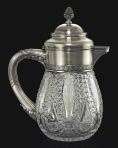 A Silver-Mounted Cut-Glass Jug   Marked K. Fabergé with the Imperial warrant, Moscow, 1908-1917, scratched inventory number indistinct, ?455?  The ovoid colorless glass body cut with teardrop and leaf-shaped panels alternating with triangle patterns, the collar with border of stylized leaves and anthemions, the hinged cover with pinecone finial, the interior with central glass cylinder and silver-gilt mounted stopper, with leaf-clad ribbon-tied reeded handle