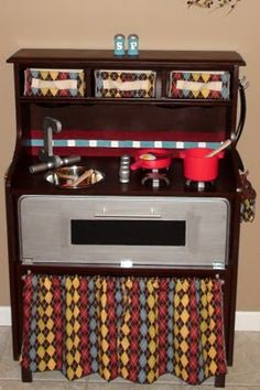 Play kitchen made from an old desk - has an oven, oven mitts, fabric baskets for storage, salt & pepper shakers, working under-cabinet lighting, & more!