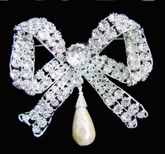In July 1893 The Committee of the Kensington wedding gift fund representing the inhabitants of Kensington visited Princess May of Teck's home at White Lodge, Richmond, and presented her with this bow shaped diamond brooch with a large oriental pearl drop.  She wore the brooch at King Edward VII's coronation in 1902 and at her own coronation in 1911 as an appropriate symbol of her childhood at Kensington Palace.
