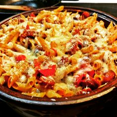Penne rigate with sausages in tomato sauce topped with mozzarela.