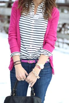 striped blouse and bright pink cardigan with a statement necklace.