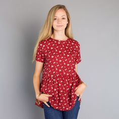 """Lightweight print top with short sleeves and bottom ruffle Approximate bust measurement: Small - 34""""      Medium - 36""""      Large - 38"""" Approximate length: Small - 26.5"""" Medium - 27"""" Large - 27.5"""" Fabric content: Polyester"""