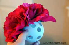 Oh, I am in LOVE with this idea!  Easy way to make hanging flower balls. Wiffle balls from dollar store,  dollar store fake flowers, pull the stems off the flower, hot glue around the circle in the wiffle ball, press flower into the hole making sure the bottom of the flower, keep going until the ball is full of flowers, then hang with a ribbon. Genius!