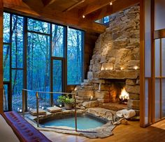 rock fireplace, indoor hot tub, floor-to-ceiling windows and a view of the woods