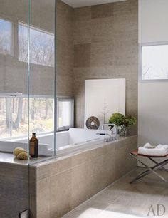 The master bath is tiled in limestone and includes a Starck tub by Duravit with Vola fittings | archdigest.com