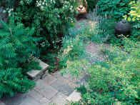 Squared stone slabs paired with granite pavers offer an example of a natural paving choice suited for a smaller garden landscaping design.