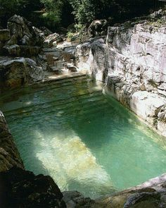 Natural pool carved into rockface. Would be an amazing retreat and private space. Natural filtering would be very difficult and hard to tell what kind of stone that is that would tolerate chemicals but interesting concept.