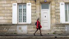 Femme qui marche dans la rue habillée d'un imperméable rouge, d'une jupe courte noire et d'escarpins à hauts talons. Elle porte un sac à main noir.