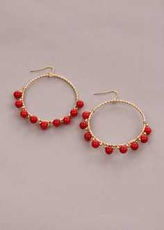 """Small red beads are wound tightly around the base of a gold hoop fastened with hook clasp making us smile. The perfect pop of color for any neutral ensemble! Measures 2"""" height, 2"""" diameter. Lead and Nickel Free. $25.00"""