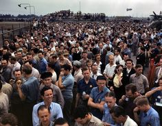 """October 1942. """"Thousands of North American Aviation employees at Inglewood, California, look skyward as the bomber and fighter planes they helped build perform overhead during a lunch period air show. This plant produces the battle-tested B-25 'Billy Mitchell' bomber, used in General Doolittle's raid on Tokyo, and the P-51 'Mustang' fighter plane, which was first brought into prominence by the British raid on Dieppe."""""""