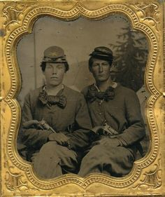 """A sixth plate tintype of a pair of seasoned Federal cavalryman. The pair sit dressed nearly identical. Each sporting large silk cravats and caps with cavalry insignia, company and regimental id pinned to the top. It looks to be maybe """"22"""" up there on top of the cap. Each man has a massive Colt Army tucked into his belt. (Continued in comments.)"""