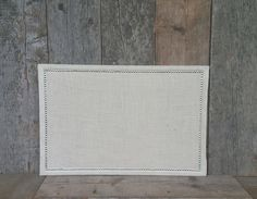 Decorate and organize your work or living space at the same time with this pin board covered in a lovely cream-colored burlap. The silver border adds a classy touch to the rustic feel of burlap. This corkboard measures 24x36 inches and hangs vertically or horizontally from a black ribbon or jute rope tie (according to selection at checkout).  The burlap is steam ironed flat and attached with a strong adhesive to ensure a smooth, tight surface. The back is neatly finished with a natural…