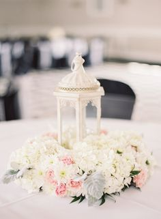 Ivory lanterns with a wreath of fresh white hydrangea and cushion mums with pink roses and dusty miller wedding Centerpieces