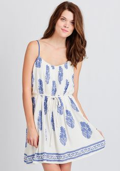This lovely ivory-hued frock features a blue intricate floral print allover with a blocked floral print at the hemline.