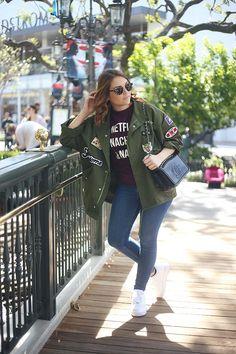 Look calça jeans skinny, camiseta Netflix, jaqueta militar com patches, óculos de sol, tênis Nike branco, bolsa preta Chanel, Los Angeles, California.