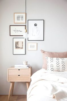Bedroom with light grey walls, light wood, pastel accents and a gallery wall over the bed side table