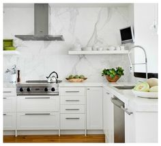 Well appointed white kitchen features walls lined with white IKEA cabinets donning long satin nickel pulls and white marble countertops holding a cooktop under a stainless steel hood flanked by white floating shelves mounted on a white marble slap backsplash.