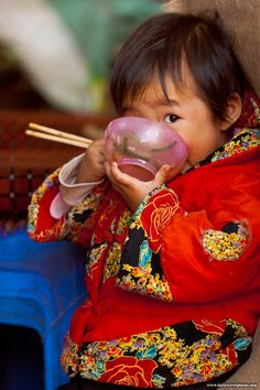 Dubious Deadeye - A young Chinese girl plants her face in her food bowl while keeping a wary eye on the photographer (ARCHIVED PHOTO on the weekends - originally photographed 2007/09/30). - Lijiang, Yunnan, China