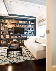 Great neutral sofa and loud area rug..also like the idea of the deep color used for the built in bookcase.