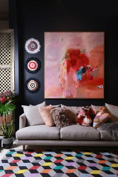 Dark walls are lifted with bright artwork and a colourful rug. This living space is filled with textures, layers and contrasts.