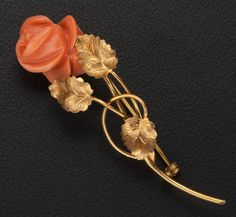 A brooch featuring a carved coral rose on a 18k gold stem.