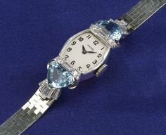 Lady's Aquamarine and Diamond Wristwatch, Raymond Yard, c. 1940, the silvertone dial with Arabic numeral indicators, the shaped platinum case set with fancy-cut aquamarines and diamonds, enclosing a Movado 17-jewel movement, completed by a later 14kt white gold bracelet, lg. 7 3/8 in.