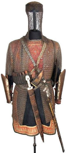 A complete Khevsur armor including a handwoven gambeson, a riveted mail misiurka-type helmet, a butted mail shirt, a pair of hand forged steel arm guards. A fine cross-belt mounted with hammered silver plaques, a large kindjal dagger, a distinctive khmali sword, a miquelet pistol, a leather bandoleer with powder tubes with a horn priming flask, a nagaika crop, a typical Khevsur shield, a pair of original rawhide shoes. late 17th-late 19th century. Medieval World, Medieval Armor, Medieval Fantasy, Arm Armor, Body Armor, Empire Moghol, Arm Guard, India, Middle Ages