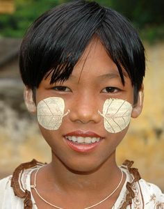 """A girl near the """"U Bein's Bridge"""" in the small town of Amarapura, BURMA. She wears tanaka paste (made from ground bark) on her face which serves as a sunscreen, to provide a cooling sensation, to remove acne, and to promote a smooth skin. It is also believed to have anti-fungal properties. Tanaka is commonly used among the people of Burma. While most people apply tanaka all over their faces or with a few strokes over the nose and cheeks, this girl has a creative pattern of a leaf on each…"""