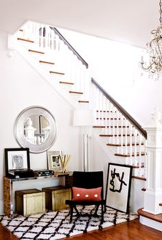 White entryway with round chrome mirror