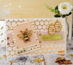 Make this cute wooden bee the showcase of your card by framing it! - made using the beautiful Dovecraft Bee Happy collectionTrim a 5x7 card to 11cm tall (fold at top)Trim a piece of honeycomb paper to 17cm x 10.5cm and add to the card frontRip a piece of bee paper to approx 4cm wide and add across the middle of the cardTrim a piece of paper to 7cm x 9cm and using the WRMK frame punch board create a frameStick the frame to a piece of peach card, add to the card front towards the LH side at a…