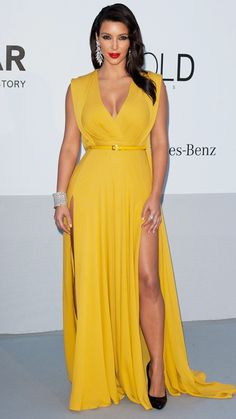 Kardashian wore a canary yellow Elie Saab gown featuring a low neck and high slit at the amfAR Gala at the 2012 Cannes Film Festival. She completed the Hollywood glam look with soft, retro waves, a bright red lip, and lots of diamonds.