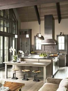 I love the look of this kitchen. The dark brick and colors tie very well with the large windows.