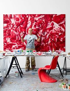 Marc Quinn, red-handed, in front of Flesh Painting (On Fat and Lean), 2013; the Verner Panton chair is by Vitra.