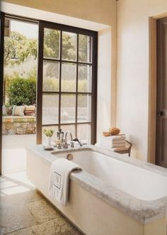 love this California style bath by Barbara Colvin with the stone floors and French doors. LOVE.